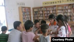 立人志愿者陈扬跟孩子们一起猜谜语。 (立人网站图片)