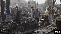 Warga Irak memeriksa lokasi ledakan akibat serangan roket terhadap kawasan permukiman di Baghdad (5/7).
