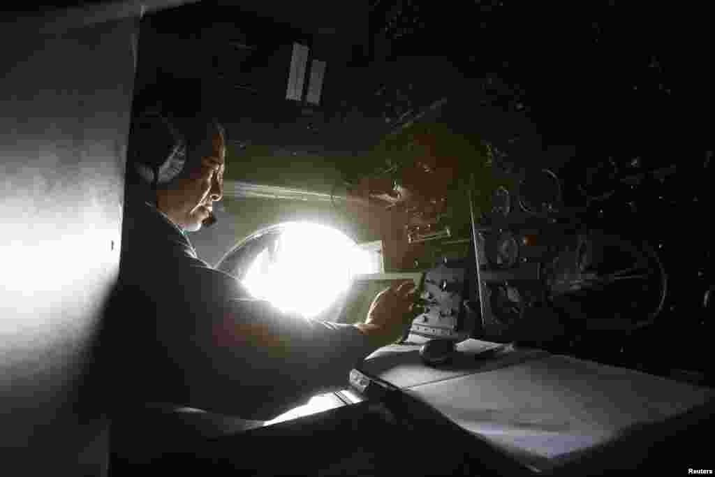 Military officer Duong Van Lanh works onboard a Vietnamese airforce AN-26 during a mission to find the missing Malaysia Airlines flight MH370 off Tho Chu islands March 11, 2014.