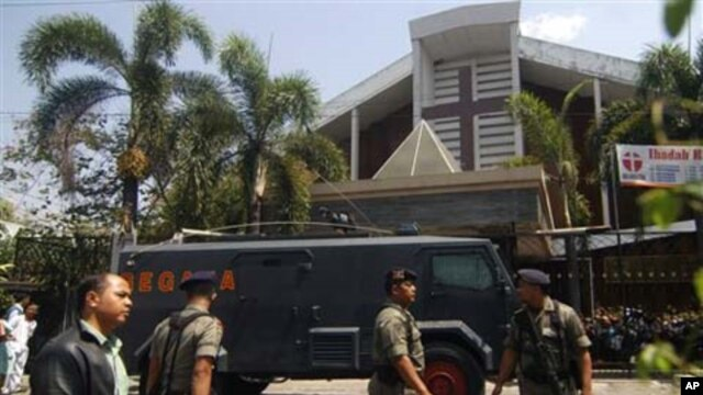 Indonesian police officer stands guard near an armored vehicle outside a church after an explosion in Solo, Central Java, Indonesia (File Photo - September 25, 2011).