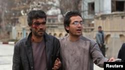 3月28日在喀布尔遭袭击的地点,一名男子在帮助一位在袭击中受了伤的人