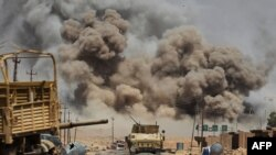 FILE - Smoke billows as Iraqi forces advance towards Al-Ayadieh village, the last remaining active front line near Tal Afar, during an operation to retake the city from the Islamic State (IS) group on August 29, 2017.