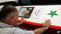 """A Syrian man mourns a relative whose picture is displayed atop his coffin with Arabic words that read: """"The Martyr, Atef Abdullah"""" during a mass funeral procession for several Syrians killed in a twin suicide bombings, at a mosque in Damascus, Syria Satur"""