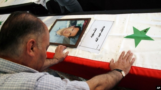 "A Syrian man mourns a relative whose picture is displayed atop his coffin with Arabic words that read: ""The Martyr, Atef Abdullah"" during a mass funeral procession for several Syrians killed in a twin suicide bombings, at a mosque in Damascus, Syria Satur"
