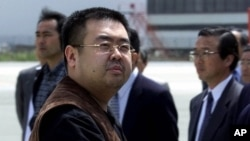 FILE - A man believed to be Kim Jong Nam, the eldest son of North Korean leader Kim Jong Il, looks at a battery of photographers as he exits a police van to board a plane to Beijing at Narita International Airport, northeast of Tokyo, May 4, 2001.