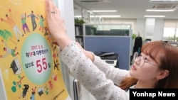 An employee puts up Election Day poster for South Korea presidential election. (Yonhap News)