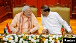 India's Prime Minister Narendra Modi (L) talks to Sri Lanka's President Maithripala Sirisena at the Presidential Secretariat in Colombo, March 13, 2015.