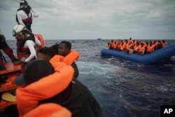 FILE - Migrants on a blue rubber boat wait to be rescued some 14 nautical miles from the coast of Libya in Mediterranean Sea, Sept. 8, 2019.