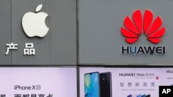 Biểu tượng của Apple và Huawei được trưng bày bên ngoài cửa hàng bán diện thoại di động tại Thâm quyến tỉnh Quảng Đông (ảnh chụp ngày 7/3/2019)