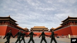 Soldiers wearing protective face masks march past the closed entrance gates to the Forbidden City, usually crowded with tourists before the new coronavirus outbreak in Beijing, Thursday, March 12, 2020. For most people, the new coronavirus causes…
