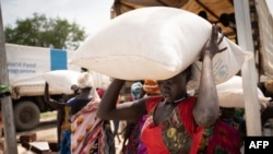 Women from Murle ethnic group carry bags of sorghum during a food distribution by United Nations World Food Program in Gumuruk, South Sudan, June 10, 2021.