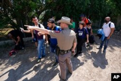 FILE - A Texas Department of Public Safety officer directs a group of migrants who crossed the border and turned themselves in, in Del Rio, Texas, June 16, 2021.