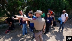 FILE - A Texas Department of Public Safety officer directs migrants who crossed the border and turned themselves in, in Del Rio, Texas, June 16, 2021.