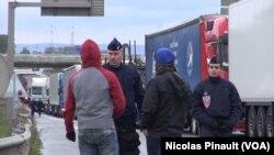 """Des policiers français parlent à deux migrants près de la """"jungle"""" de Calais, France (Nicolas Pinault/VOA)."""