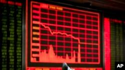 在北京一家证券交易公司,有人观看电子屏幕上的股票信息,屏幕两侧的股价一片惨绿(2016年1月4日)