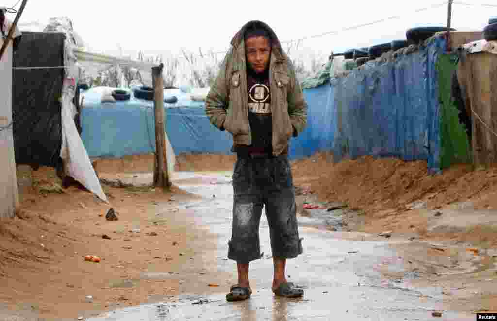 一名男孩2013年1月31日在黎巴嫩南方提尔地区的一个难民营地以外衣遮雨,在雨中行走。
