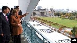 La chancelière allemande Angela Merkel, à droite, debout à côté du vice-président de la Chine, Xi Jinping, à gauche, à la chancellerie de Berlin, en Allemagne, le 12 octobre 2009. Elle pointe son doigt vers le bâtiment du parlement allemand Reichstag