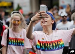 A participant takes pictures during a gay pride parade in Bucharest, Romania, June 9, 2018. People taking part in the parade demanded more rights and acceptance for same-sex couples.