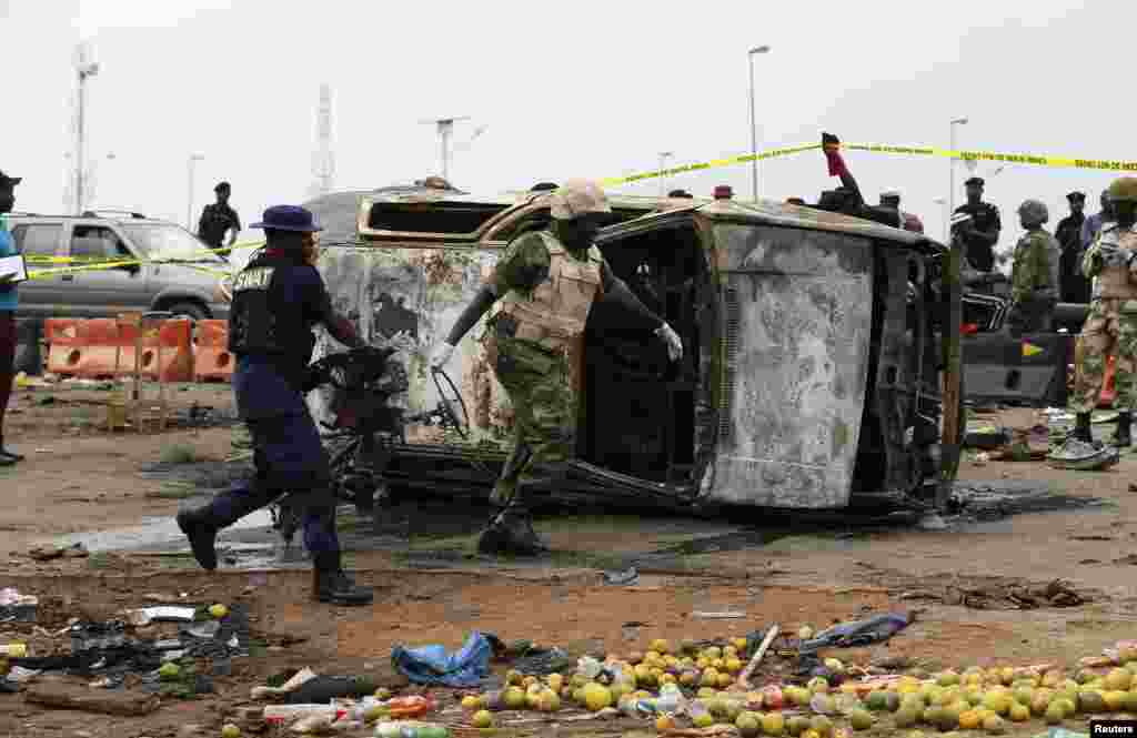 A soldier and a paramilitary officer help to move part of a damaged car at the scene of a car bomb attack in Nyanya, Abuja, Nigeria.