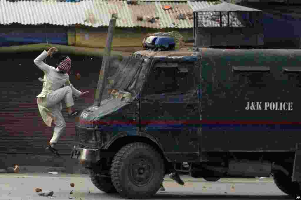 A masked Kashmiri protester jumps on the bonnet of an armored vehicle of Indian police as he throws stones at it during a protest in Srinagar, Indian-controlled Kashmir.
