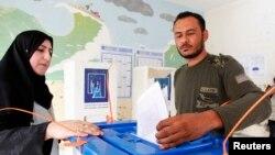 伊拉克進行議會選舉,一名男子將他的選票放進票箱。