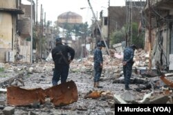 Iraqi Federal police tour a neighborhood shortly after a battle, still littered with rubble and bodies of militants in Mosul, Iraq on March 16, 2017.
