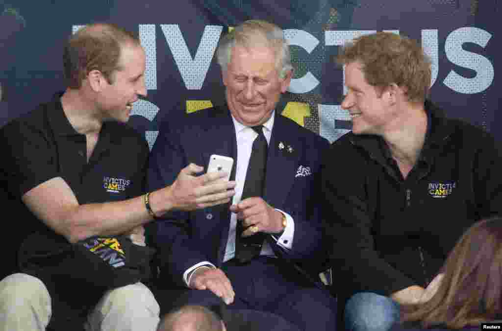 Britain's Princes William (L), Charles (C) and Harry look at a mobile phone during the Invictus Games in the Lee Valley Athletics Centre in north London, England.