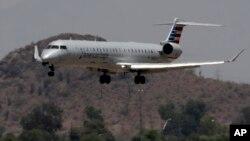Sebuah pesawat jet American Eagle tampak harus melewati gelombang udara panas saat mendaraat di bandara Sky Harbor di Phoenix, Arizona Senin (19/6).