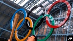 2012年伦敦奥运会组委会主席塞巴斯蒂安·科举起接力火炬(2011年6月8号资料照)