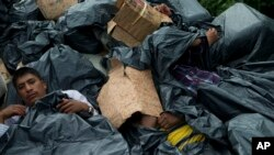 FILE - Central American migrants use trash bags and cardboard to protect themselves from the rain as they wait atop a stuck freight train, outside Reforma de Pineda, Chiapas state, Mexico, June 20, 2014.