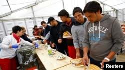 Migranti dobijaju hranu u improvizovanom skloništu u sportskoj hali u Hanau u Nemačkoj, 22. septembra 2015.