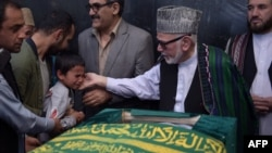 Ten year-old Mustafa, son of Afghan reporter Zabihullah Tamanna,(2L), relatives and friends pray around the coffin during a ceremony at a military hospital in Kabul on June 7, 2016.