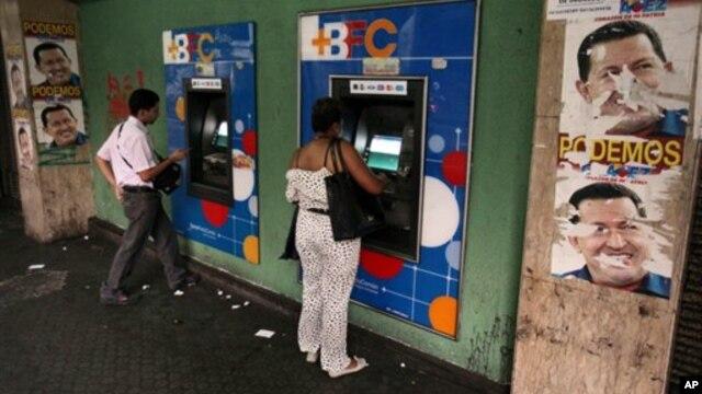 Warga Venezuela menarik uang tunai dari mesin ATM di Caracas, Venezuela (8/2). Pemerintah Venezuela mengumumkan devaluasi (penurunan nilai) mata uang bolivar terhadap dolar menjadi enam koma 30 bolivar untuk satu dolar, yang mulai berlaku hari Rabu pekan mendatang.
