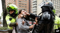 FILE - Police detain a man who was blocking traffic during a protest against a decree by Colombia's President Ivan Duque allowing police to confiscate any amount of drugs from people in the street in Bogota, Colombia, Sept. 6, 2018.