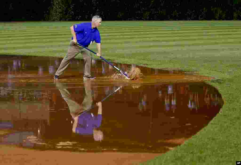 A member of the grounds crew works on the field soaked with heavy rain water at Wrigley Field in Chicago, Illinois, USA, Aug. 19, 2014.