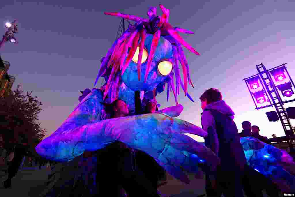 A boy looks at a six-meter tall luminescent puppet, operated by ten performers, during a preview of Vivid Sydney, promoted as the world's largest festival of light, music and ideas.