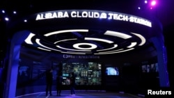 FILE - Visitors stand inside a booth introducing Alibaba Cloud services at an exhibition venue during Alibaba Group's 11.11 Singles' Day global shopping festival in Shenzhen, China, Nov. 11, 2016.