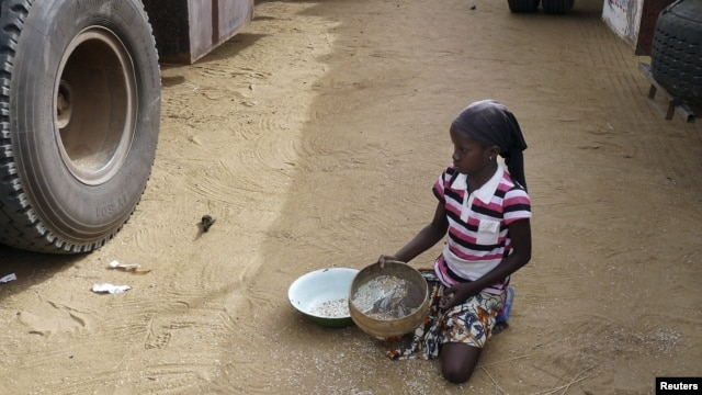 A girl gathers rice spilled from a humanitarian food convoy in the northeastern city of Gao, Mali, June 14, 2012.