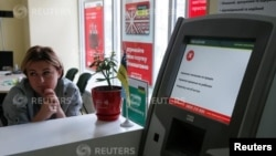 An employee sits next to a payment terminal out of order at a branch of Ukraine's state-owned bank Oschadbank after Ukrainian institutions were hit by a wave of cyber attacks earlier in the day, in Kyiv, June 27, 2017.