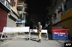 An Indian paramilitary trooper stands guard at a roadblock at Maisuma locality in Srinagar, Aug. 4, 2019.
