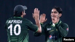 Pakistan's Shahid Afridi (L) congratulates Mohammad Hafeez as he dismissed Bangladesh's Shahriar Nafees successfully during their second One Day International, ODI cricket match of the series in Dhaka December 3, 2011. REUTERS/Andrew Biraj (BANGLADESH - T
