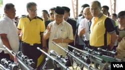 Ketua Fron Pembebasan Islam Moro (MILF), Haji Murad Ebrahim (tengah) menunjukkan kepada Presiden Filipina Benigno Aquino berbagai senjata pemberontak yang diserahkan di kota Sultan Kudarat, Maguindanao, Filipina selatan, Selasa (16/6).