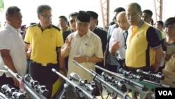 Ketua Front Pembebasan Islam Moro (MILF) Al Haj Murad Ebrahim (tengah) menunjukkan kepada Presiden Filipina Benigno Aquino (kanan) senjata-senjata yang digunakan para pemberontak dalam proses pembicaraan damai di Sultan Kudarat, provinsi Maguindanao, FIlipina, 16 Juni 2015 (Foto: dok).