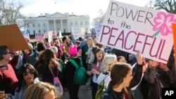FILE - Women's March demonstrators walk past the White House in Washington, Jan. 20, 2018. (AP Photo/Pablo Martinez Monsivais)
