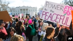 Women's March demonstrators walk past the White House in Washington, Jan. 20, 2018.
