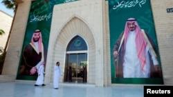 Men walk past murals depicting Saudi Arabia's King Salman bin Abdulaziz Al Saud and Crown Prince Mohammed bin Salman, in Riyadh, Saudi Arabia, Nov. 9, 2017.
