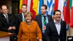 Le Premier ministre grec Alexis Tsipras, à droite, marche avec la chancelière allemande Angela Merkel, au centre, en partant du sommet européen à Bruxelles, le 8 mars 2016. (AP Photo/Virginia Mayo)