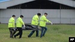 Petugas polisi membawa satu dari dua jenazah penumpang gelap yang jatuh dari ruang roda pesawat yang sedang lepas landas di Bandara Jose Joaquin de Olmedo di Guayaquil, Ekuador, Senin, 26 Februari 2018.