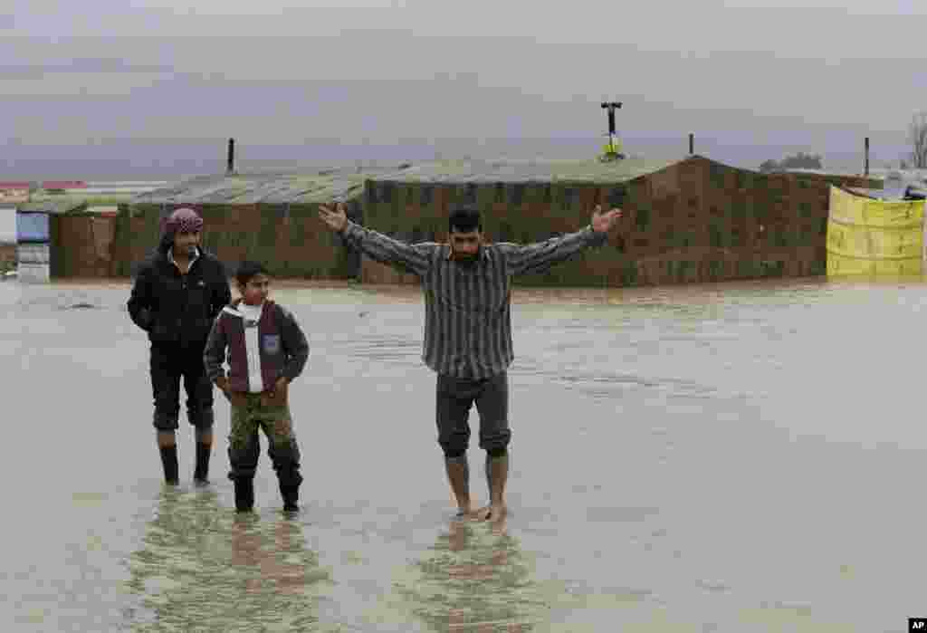 A Syrian refugee, right, gestures as he stands in flooded water at a temporary refugee camp, in the eastern Lebanese Town of Al-Faour near the border with Syria, January 8, 2013.
