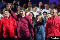 Venezuela's President Nicolas Maduro and his wife Cilia Flores wave to supporters after the National Electoral Council announced that with almost 93 percent of polling stations reporting, Maduro won nearly 68 percent of the votes in Sunday's election, beating his nearest challenger Henri Falcon by almost 40 points, in Caracas, Venezuela, May 20, 2018.
